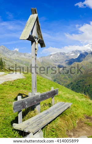 wooden bench and cross in european alp mountains - stock photo