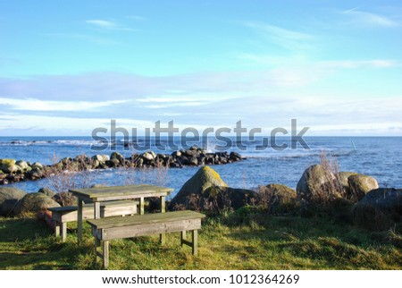 Wooden bench and table by seaside a sunny day by the coast of the swedish island Oland in the Baltic Sea