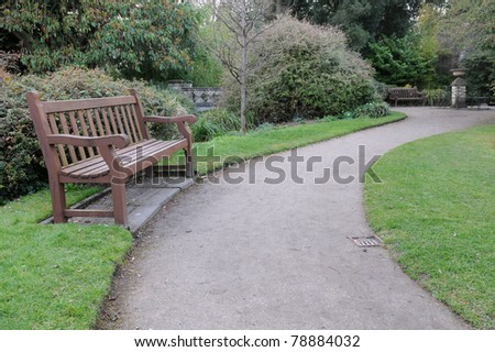 Wooden Bench and Winding Path in a Tranquil Garden - stock photo