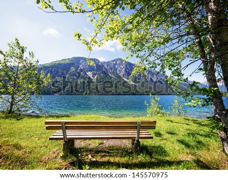 wooden bench at a lake - stock photo