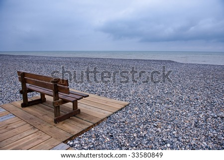 Wooden bench at a pebbles beach on a cloudy day