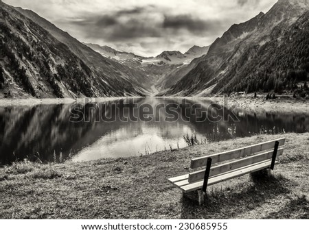 wooden bench at a reservoir in austria - stock photo