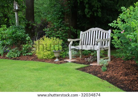 Wooden bench in a beautiful park garden. - stock photo