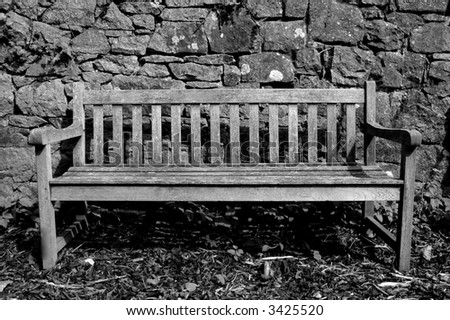 Wooden bench in front of granite wall - stock photo