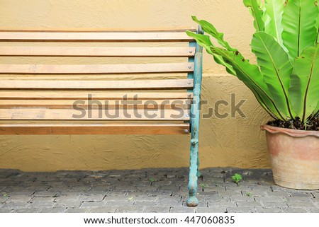 Wooden bench in outdoor scene with flower pot in orange wall