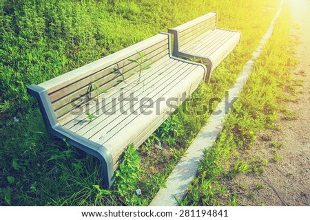 Wooden bench in park with vintage color. - stock photo