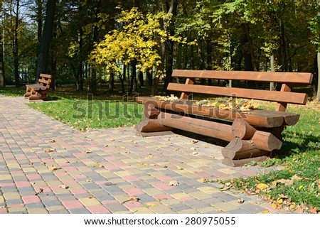 Wooden bench in the autumn park - stock photo