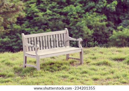Wooden bench in the park with vintage style. - stock photo