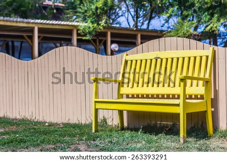 Wooden bench near wood fence under blue sky - stock photo