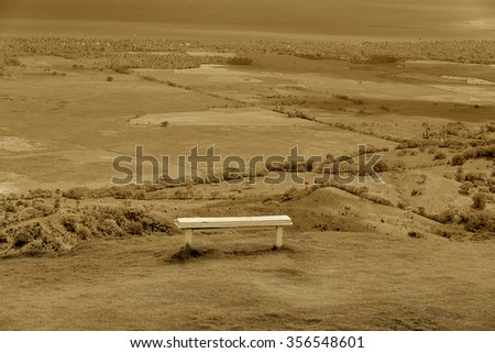 wooden bench on a hilltop overlooking the horizon