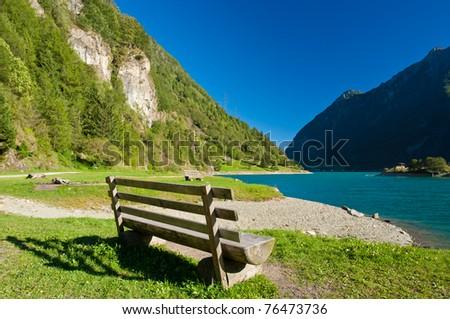 wooden bench on a lake shore on a sunny spring day, lago di poschiavo, ticino canton - stock photo