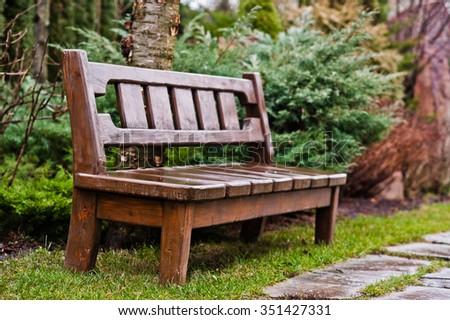 Wooden bench on garden  - stock photo