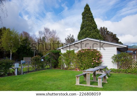 Wooden bench on lush green lawn with trees and house - stock photo