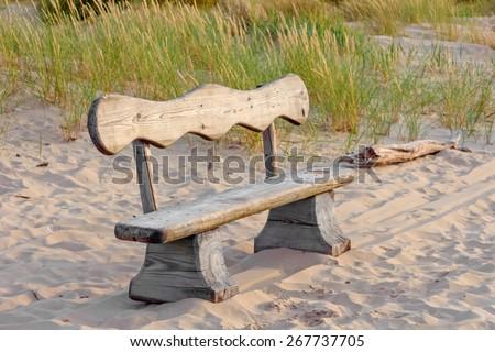 Wooden bench on summer sandy beach in sunset light - stock photo