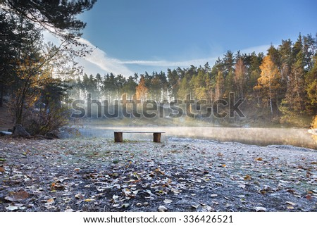 Wooden bench on the lake shore in the background sunlight, trees and rocks. - stock photo