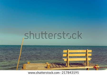 wooden bench over pier dock jetty with relaxing ocean view caye caulker belize caribbean - stock photo