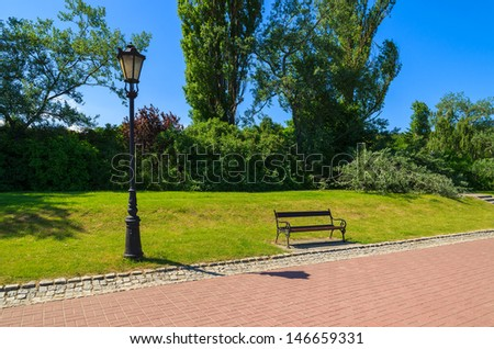 Wooden bench park tourist promenade green tree grass summer day, Gdynia Orlowo, Baltic Sea, Poland  - stock photo