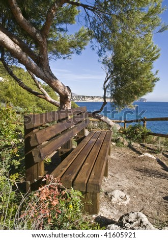 Wooden bench with a wonderful view to the Mediterranean coast of Spain - stock photo