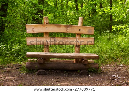 Wooden bench with backrest in a forest. Spring season. Green vegetation around. - stock photo