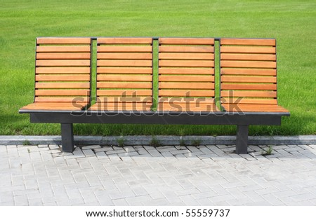 Wooden benches against the background of green grass - stock photo