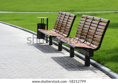 Wooden Benches Against The Background Of Green Grass