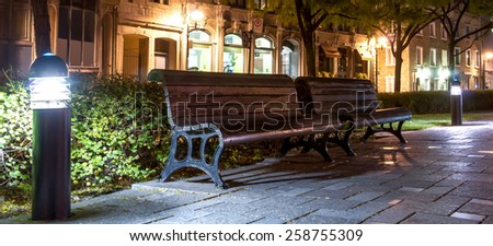Wooden benches in a pedestrian rest area with floor lamps in Old Montreal at night. - stock photo