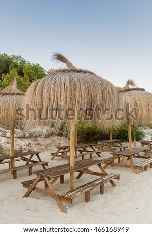 Wooden benches with grass parasols on the beach
