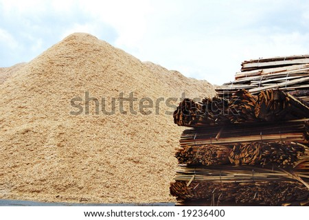 Wooden biomass chips and lumber material - stock photo