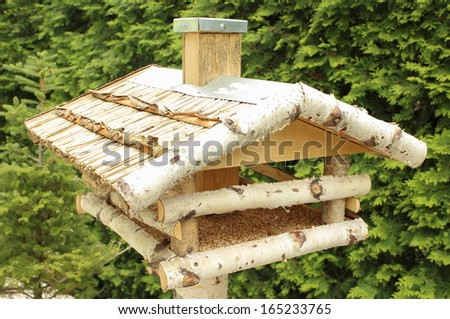 Wooden bird feeder with seeds on green background - stock photo