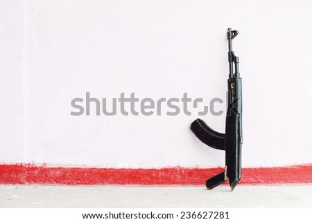 Wooden black toy Kalashnikov rifle leaning against pink wall - stock photo