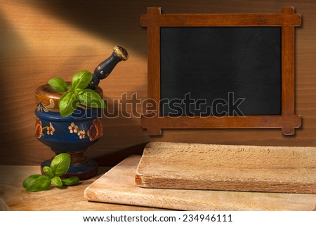 Wooden Blackboard in the Kitchen / Rustic and empty blackboard, old wooden mortar and pestle with basil leaves on wooden wall with chopping board - stock photo