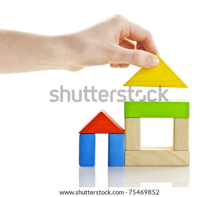 Wooden block houses under construction isolated on white background - stock photo