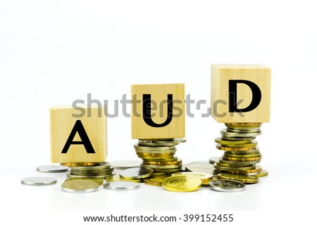 Wooden block with stacked coins with word AUD (Australian Dollar) country currency code
