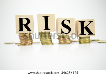 Wooden block with stacked coins with word Risk written