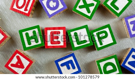 Wooden blocks forming the word HELP in the center - stock photo