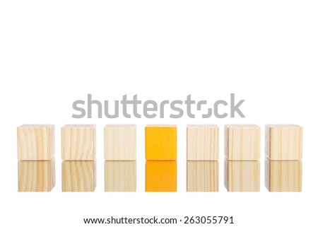 wooden blocks standing in line with orange one in the centre - stock photo
