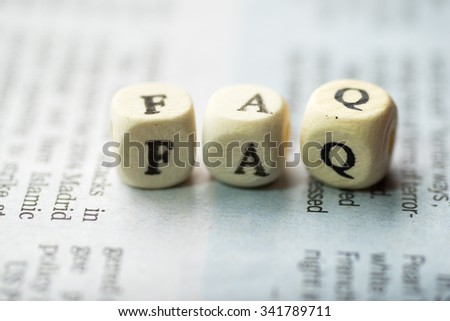 Wooden blocks with the text, FAQ on the newspaper - stock photo