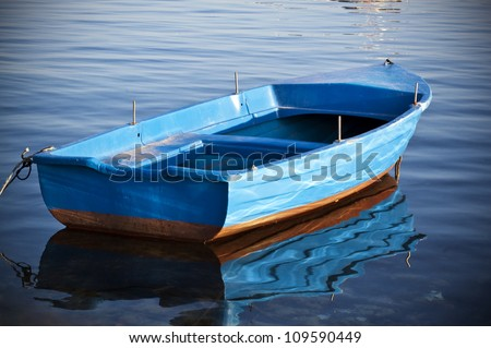 Wooden blue and empty boat of a fisherman in a still and calm water - stock photo