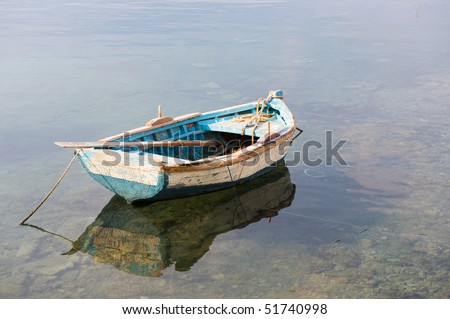 Wooden blue row boat in calm water - stock photo