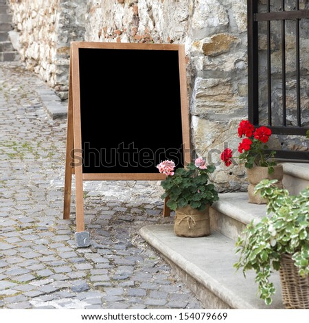Wooden board for restaurant menu with empty space to add text standing at restaurant entrance with flower pots - stock photo
