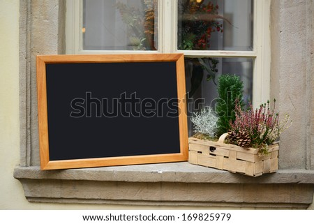 Wooden board for restaurant menu with empty space to add text standing on widnow - stock photo