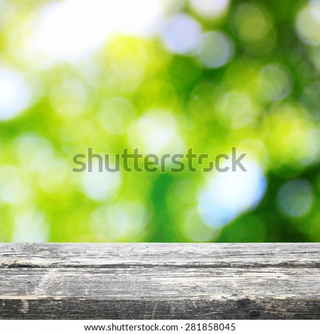 Wooden board table with bokeh summer background - stock photo