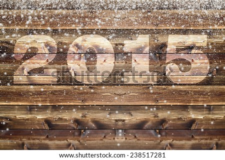Wooden board with bleached out 2015 letter and falling down fluffy snow flakes of different size - stock photo