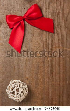 Wooden board with red ribbon and straw ball