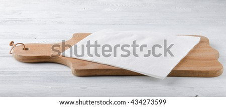 Wooden board with white napkin on the table. - stock photo