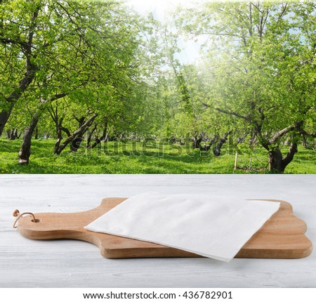 Wooden board with white napkin on the table Garden. - stock photo