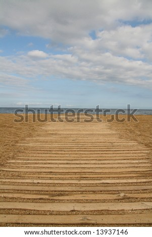 wooden boards path on the sand on a beach, blue horizon - stock photo
