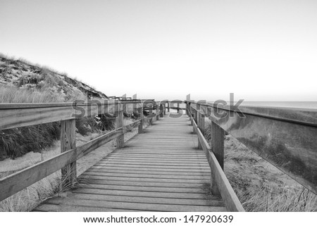 Wooden boardwalk between grassy dunes in the dawn - stock photo