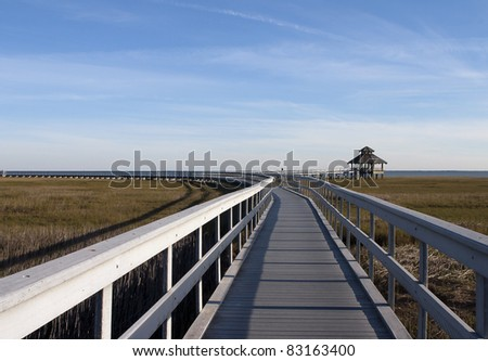 Wooden boardwalk going out to a gazebo overlooking the marsh lands - stock photo