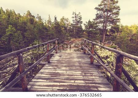 Wooden boardwalk in the forest. Instagram filter. - stock photo